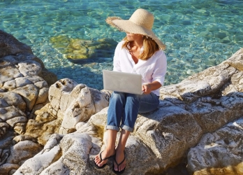 Full length portrait of casual woman working by the sea on her vacation. Middle age female sitting on the rock and typing on her laptop.