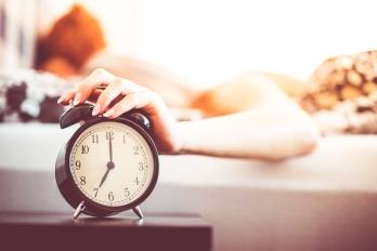 woman-shutting-off-ringing-alarm-clock-from-bed-picjumbo-com